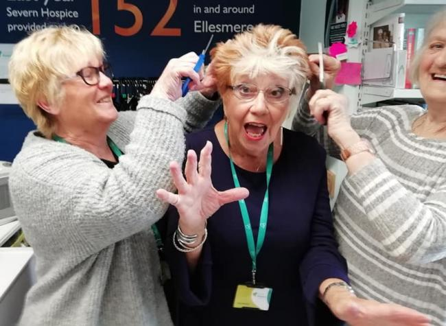 Severn Hospice volunteers with Isobel, practicing for the hair cut/shave