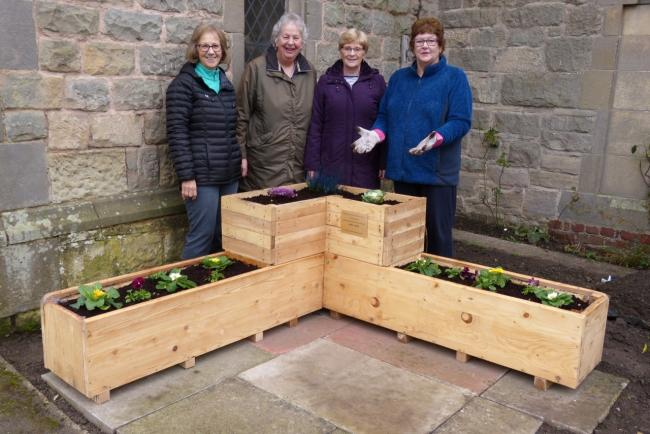 Members of Gobowen WI pictured at All Saints' Church with the planter they had commissioned to celebrate the centenary of the Shropshire Federation of WIs