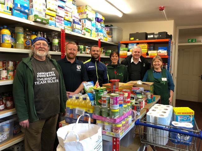 (LtoR) Lionel Parker (foodbank volunteer), Terry Rogers (FC Oswestry Town vice-chairman), Nathan Leonard (FC OSwestry Town manager), Liz Jermy (foodbank manager), Nick Maguire (FC Oswestry Town managing director) and Kath Davies (foodbank volunteer)