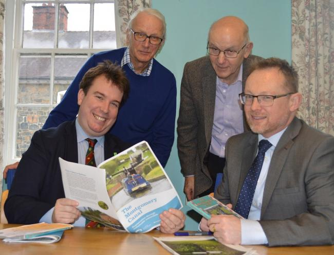 Montgomeryshire's MP Craig Williams and Assembly Member Russell George discuss the 10-year Montgomery Canal restoration plan with Montgomery Waterway Restoration Trust chair Michael Limbrey (standing left) and Montgomery Canal Partnership chair John