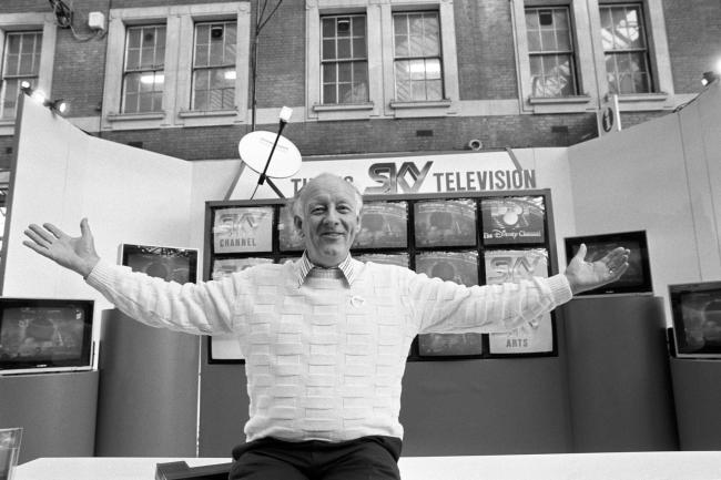 File photo dated 06/12/1989 of television presenter Frank Bough fronting a special exhibition stand at Waterloo Station in London where commuters were given a glimpse of programmes on offer from Sky Television, the satellite broadcasting station. The BBC