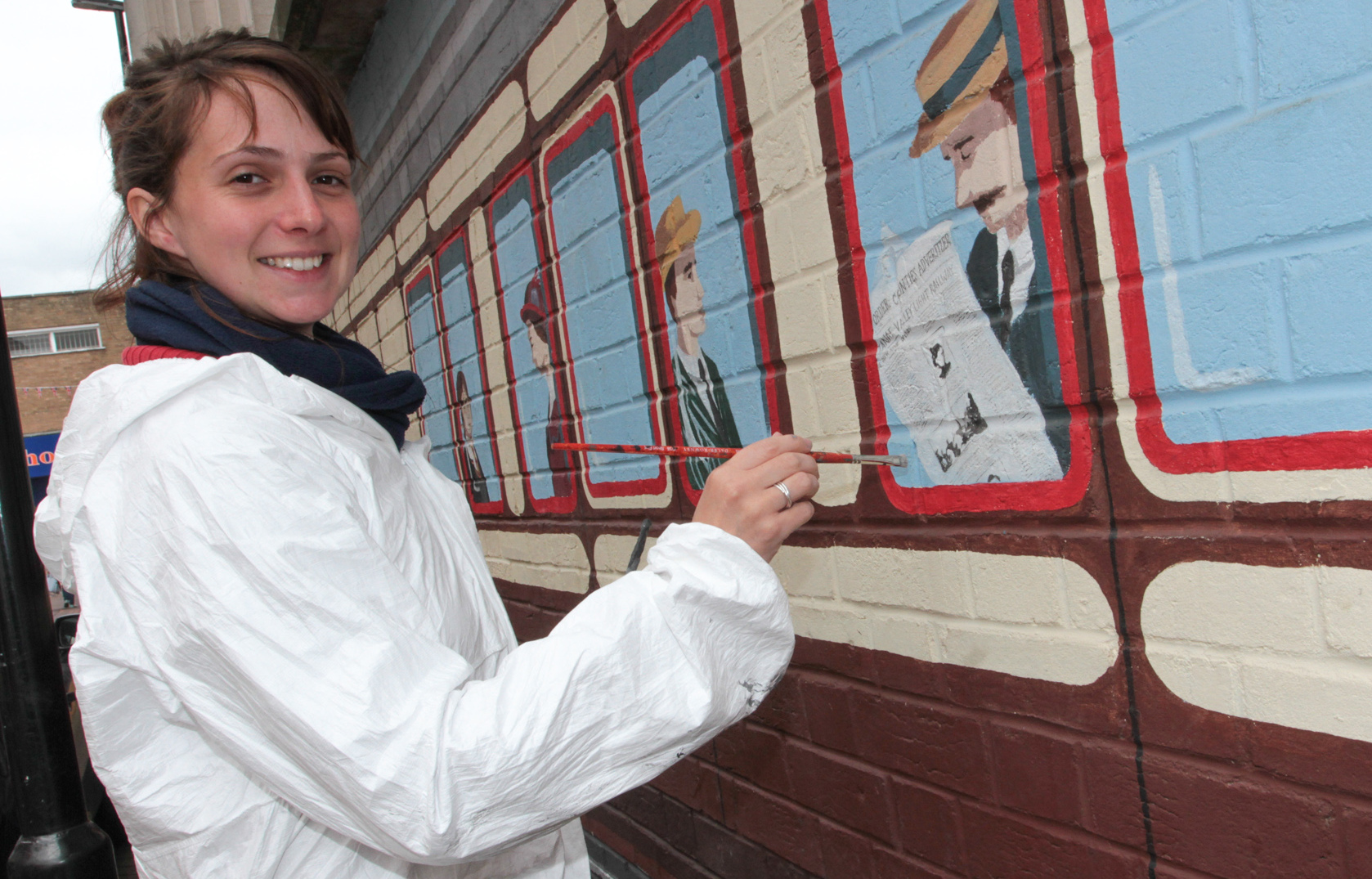 Artist, Anna Roberts, touches up her mural in New Street, Oswestry, after it was damaged by workmen during roadworks. HD060716