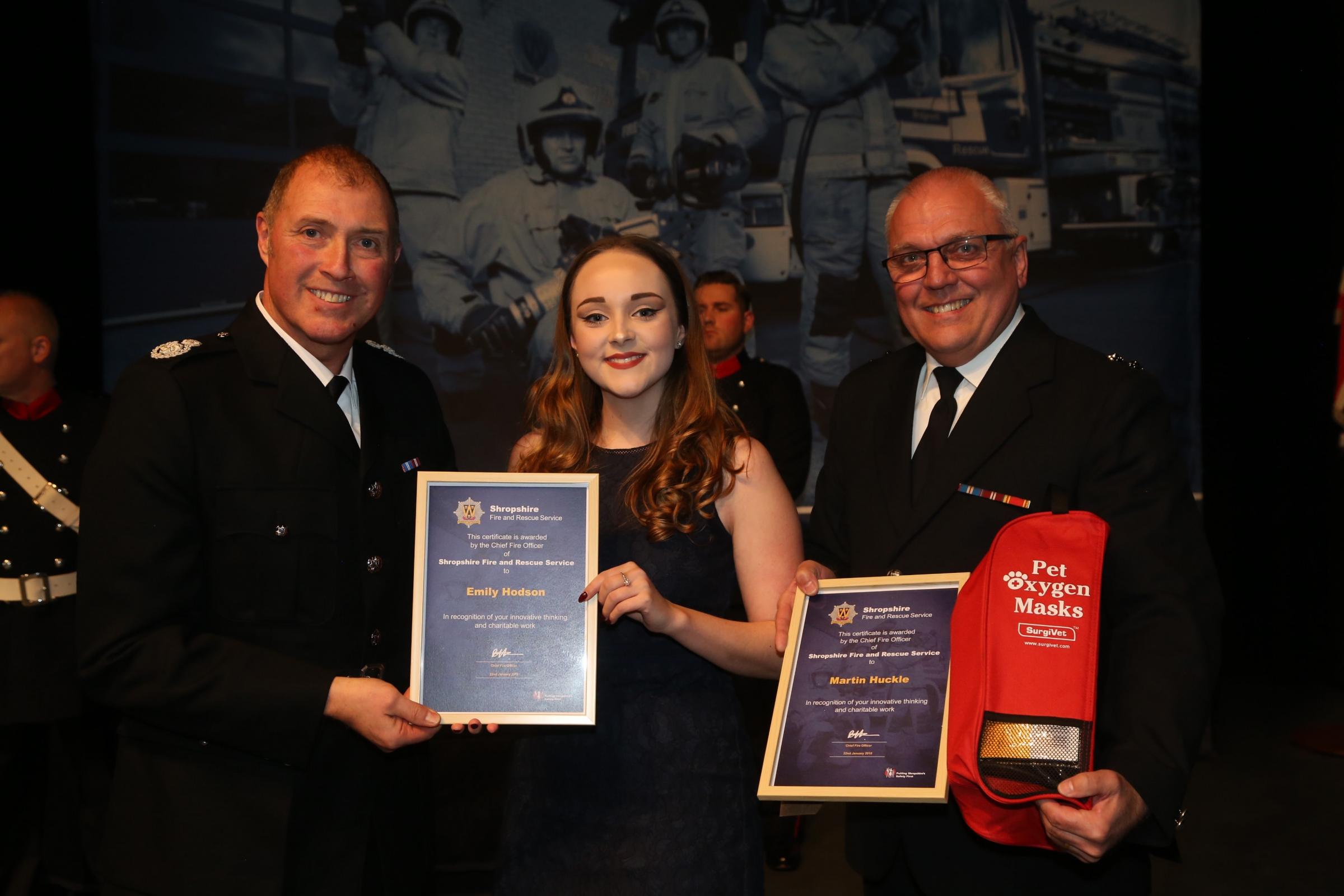Watch manager Martin Huckle and technical support officer Emily Hodson receive an award from Shropshire's assistant chief fire officer Dave Myers for raising funds for pet oxygen masks for firefighters