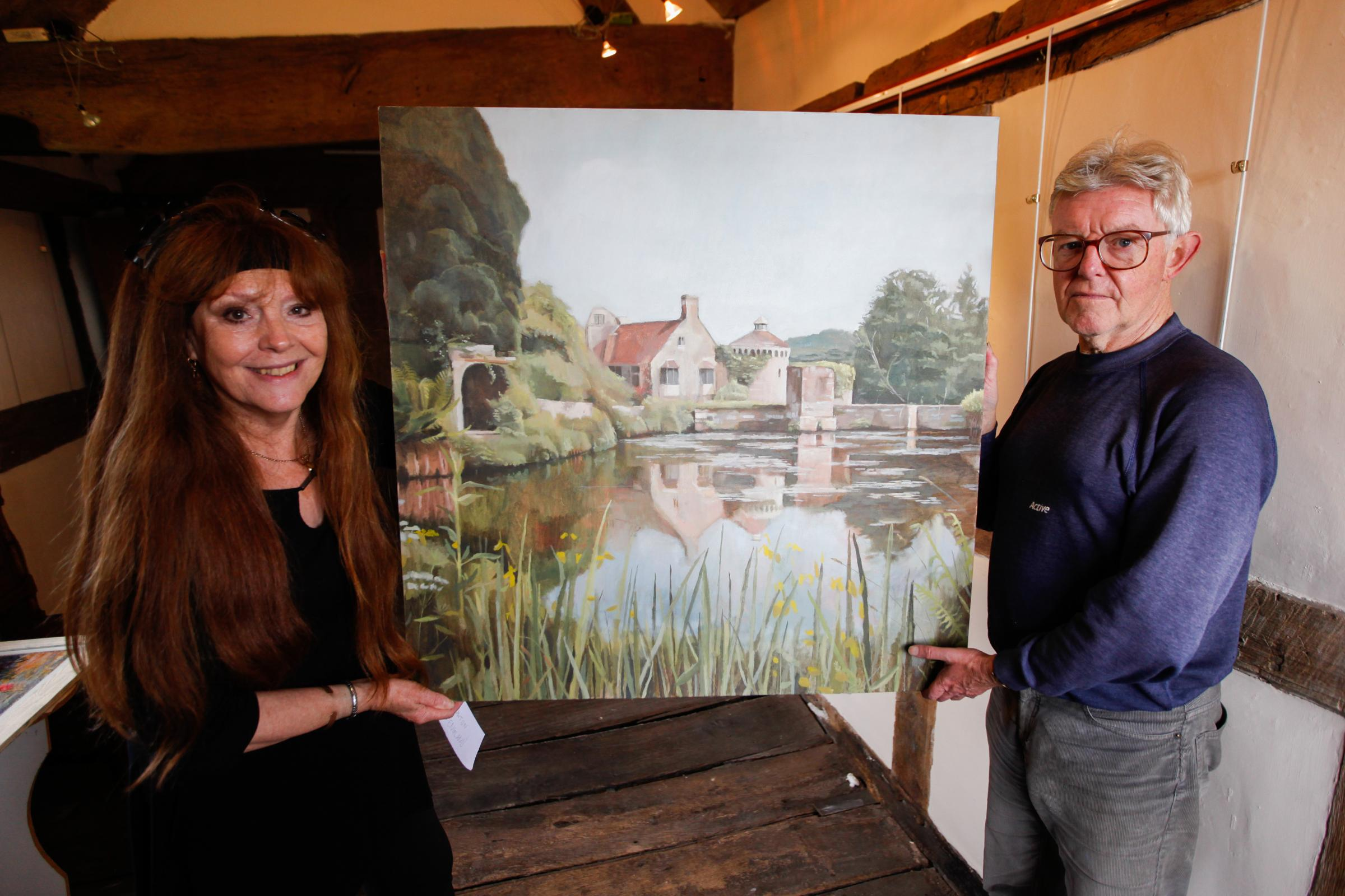 The Oswestry Visitor and Centre holds an exhibtion themed around Wilfred Owen. Pic: Exhibtion coordinator Sue Miller and Andrew Evans hand the first of thirty paintings. GA011018C.