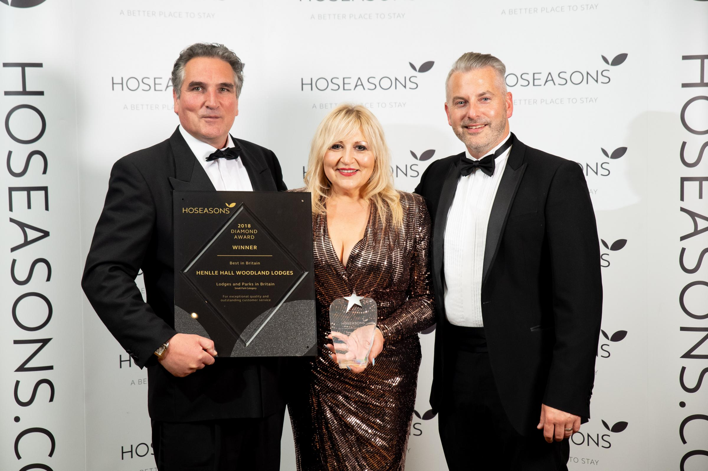 Cosmo Lloyd and Keeta Thomas, of Henlle Hall Woodland Lodges, receive their award from Hoseasons head of product, Scott Drew. Picture - Darren Cool