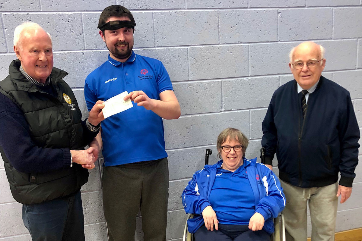 Shropshire Special Olympics group members Darren Roberts and Ann-Marie Campbell receive their cheque from Rotarians Mike Jones and Denzil Ellis