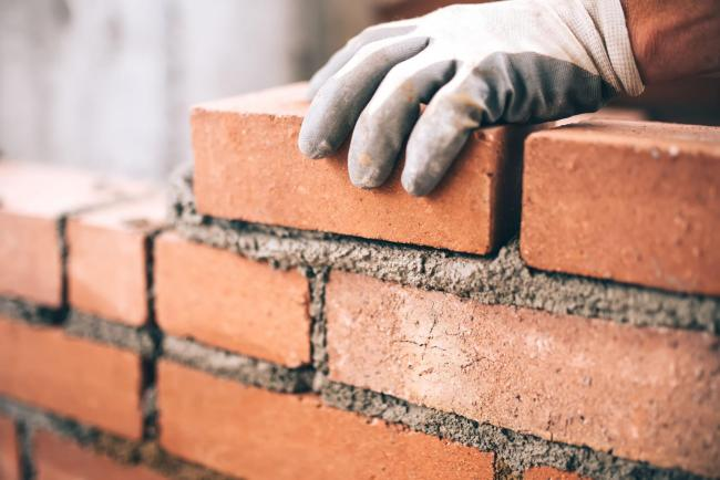 Close up of industrial bricklayer installing bricks on construction site.